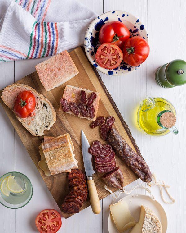 cena de San Juan al aire libre: Longaniza, fuet, queso y chorizo de león preparado sobre pan acompañado de tomates y aceitera