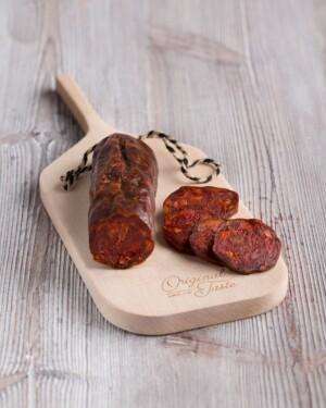 Chorizo de León ahumado, cular. Pieza entera, se muestra corte. Sobre tabla de madera de haya