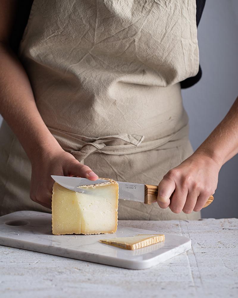 mujer cortando queso de oveja con cuchillo mango d eolivo sobre tabla de marmol blanco