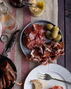 Jamón Ibérico de Cebo, Lomo Ibérico de Bellota, Foie y Chorizo de León presentados como picoteo en platos plateados con botellines y olivas