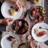 Lomo Ibérico de Bellota, Longaniza, Foie, Chorizo de León, Queso de Oveja, Jamón Ibérico de Cebo mostrado como cena entre amigos, platos, cubiertos, vasos sobre mantel a rayas