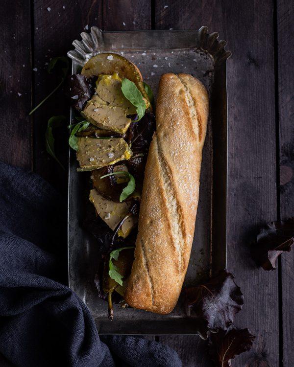 Bocadillo de Foie Gras de Pato y brotes verdes sobre bandeja metalica y fondo oscuro