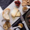 Queso de oveja, confitura, crackers e higos sobre marmol blanco y servilleta azul marino