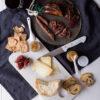 Menú para la Cena de San Juan diferente:Secallona, lomito ibérico, queso de oveja y confitura sobre mármol blanco y servilleta azul marino