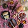 Queso de Oveja, Chorizo de León , Secallona y Fuet, servidos en platos sobre mantel a cuadros. Acompañado de picos de pan y olivas