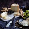 Queso Curado de Cabra y Oveja, Semicurado de Cabra y Curado de Oveja presentado sobre tabla de mármol y acompañado de moras, uvas y almendras. Cuchillo de nácar