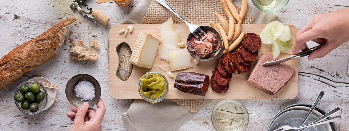 Aperitivo a la mesa de queso de oveja, chorizo de león, foie, olivas, barra de pan y picos de pan sobre tabla de madera clara y mesa blanca