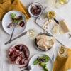 Verbena de San Juan: Jamón Ibérico de Bellota, Foie,Chorizo dulce, fuet y Queso de Cabra, presentados en mesa sobre platos y mantelería blancos. Copas d evino y cubiertos