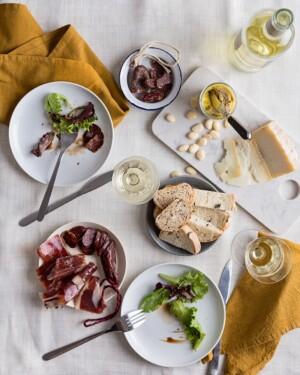 Jamón Ibérico de Bellota, Foie,Chorizo dulce, fuet y Queso de Cabra, presentados en mesa sobre platos y mantelería blancos. Copas d evino y cubiertos