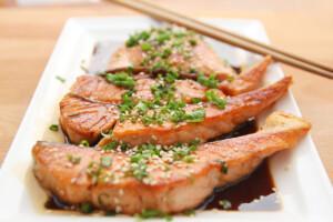 lomos de salmón cocinados en salsa de soja sobre plato blanco y palillos chinos