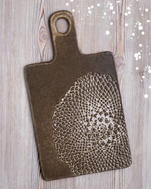 Tabla de cerámica oscura con grabado artesanal. Mango y agujero para colgar