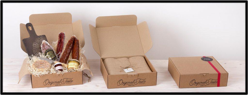 Cestas con productos gourmet, embutidos . Cajas de carton con tela de yute sobre fondo claro.